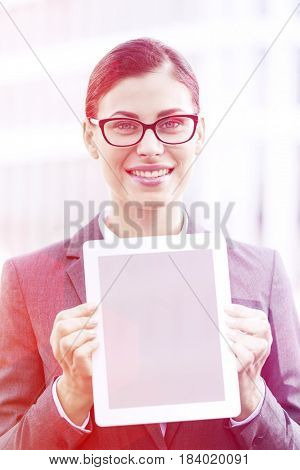 Portrait of happy businesswoman showing digital tablet outdoors