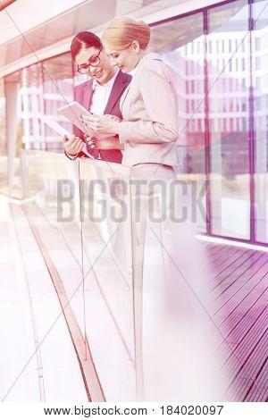 Businesswomen using digital tablet by glass railing