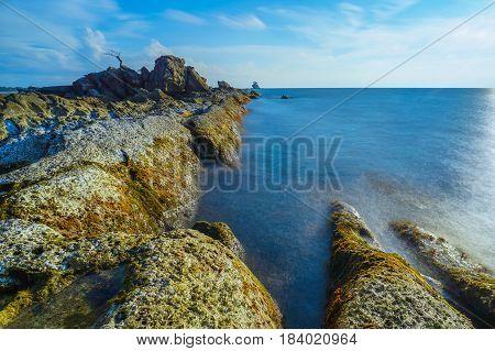 Long exposure of sea & rocks during beautiful evening at Labuan island,Malaysia.Known as Bonsai lonely tree Layang Layangan & lconic landmark in Labuan island,Malaysia.