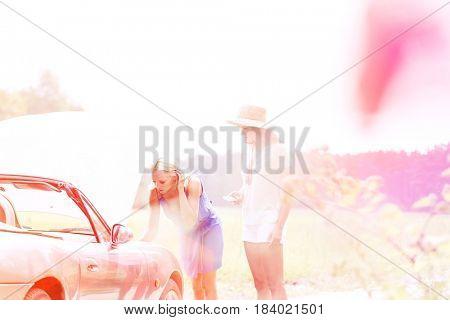 Friends repairing broken down car on sunny day