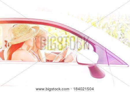 Female friends using digital tablet in car