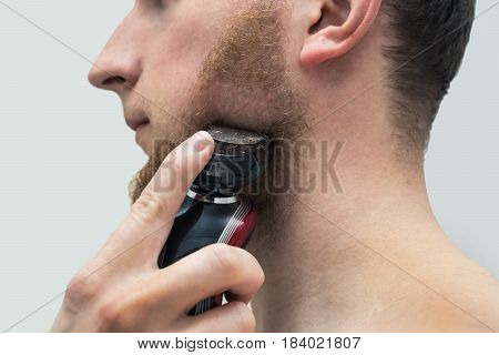 Young hipster man shaving ginger beard with electric shaver machine. Side view of shaving