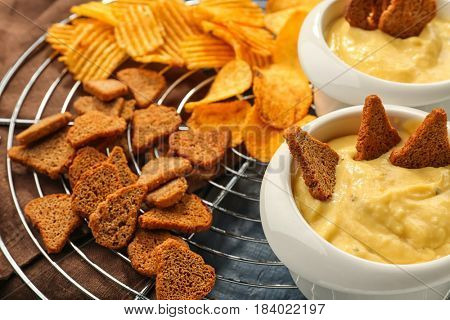 Bowl with beer cheese dip and toasts on metal stand