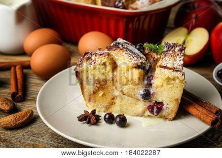Plate with piece of baked bread pudding  on wooden table