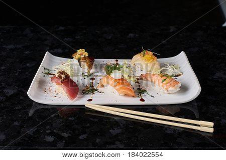 Sushi nigiri set on black marble background. Salmon, eel, prawn and tuna fish served on white plate with chopsticks.