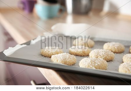 Baking tray with coconut cookies on table, closeup