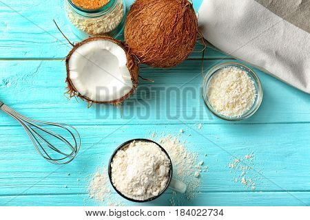 Cup with coconut flour and nuts on wooden background