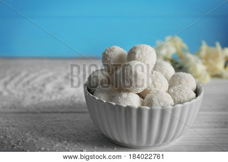 Bowl with coconut candies on wooden table