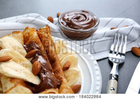 Delicious pancakes with chocolate and banana on white plate