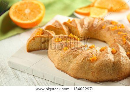 Sliced citrus cake on white wooden board