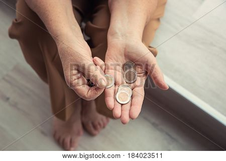 Senior woman counting coins while sitting on window sill, closeup. Poverty concept