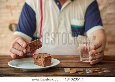Senior man sitting at table with bread, glass of water and coins, closeup. Poverty concept
