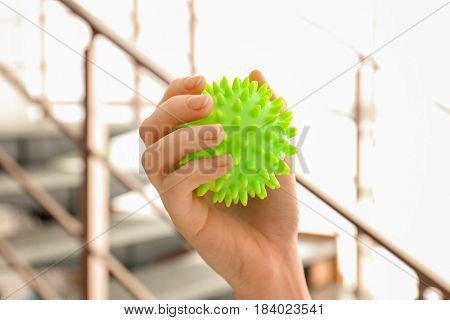 Woman holding rubber ball on blurred background