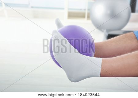 Legs of man doing exercises with rubber ball in clinic