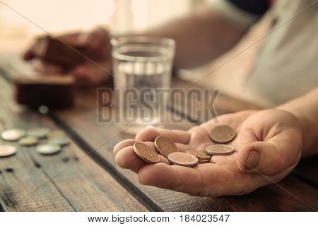 Hand of senior man with coins sitting at table, closeup. Poverty concept
