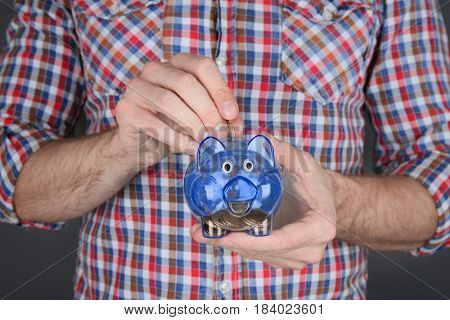 Young man putting money into piggy bank, closeup