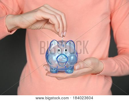 Young woman putting money into piggy bank, closeup