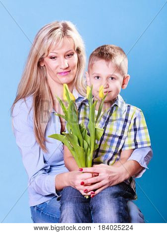 Special occasions holiday and mother day. Young boy spend time with mother celebrate together give flowers gift.