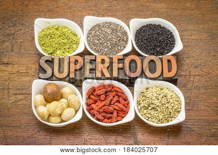 superfood abstract (matcha green tea, chia seeds, black seeds, macadamia nuts, goji berry and hemp seed hearts) with a text in vintage letterpress wood type