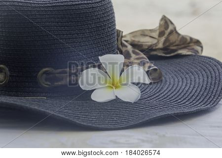 Closeup flower with hat summer on white wooden background.