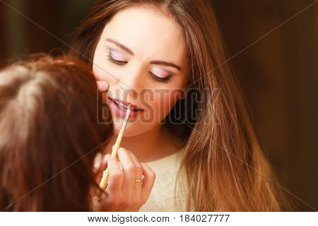 Beautician making makeup for young girl. Woman take care about look in salon