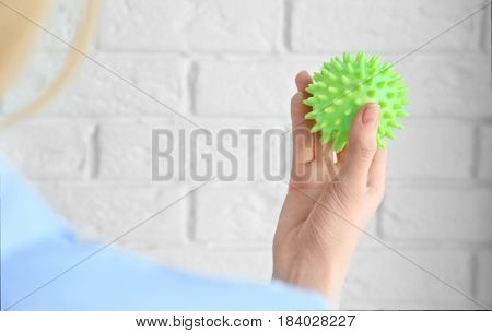 Woman holding a rubber ball against white wall