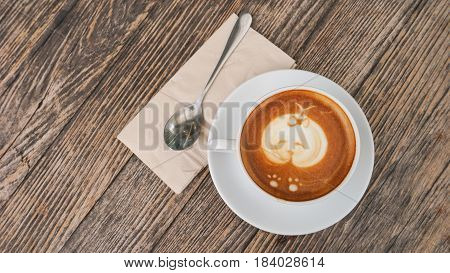 coffee cup shisu dog latte art on wooden table in coffee shop or restaurant / coffee cup blur background