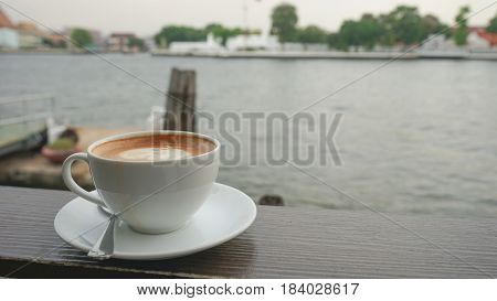 coffee cup shisu dog latte art on wooden table in coffee shop or restaurant by pier river / coffee cup blur background