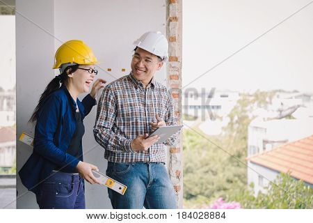 Labor Women And Engineer Smiling Discusion With  Tablet On Old Buildings In Their Job Site.