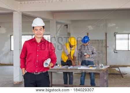 Portrait Of Confident Engineer Standing At Front Of Labor And Foreman As Discusing With Safety Helme