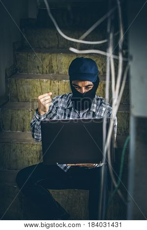 Computer Hacker Of Terrorist Stealing Information With Laptop In Abandoned Building. Low Key Photo.
