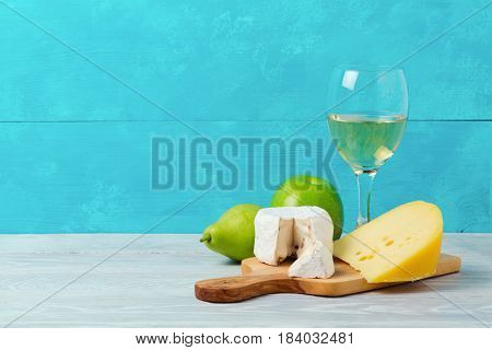 Wine and cheese with fruits on wooden table. Jewish holiday Shavuot concept.