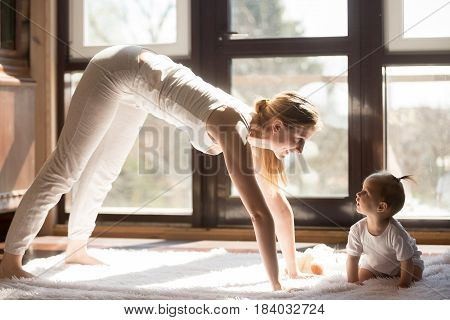 Young attractive smiling yogi mother working out, exercising, baby daughter sitting near interested, family fitness at home, wearing white sportswear, spending time together. Healthy lifestyle concept