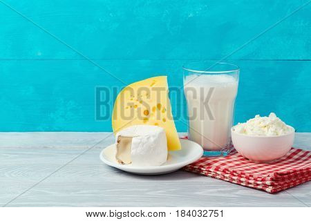 Milk and cheese on wooden table over blue background with copy space. Jewish holiday Shavuot concept