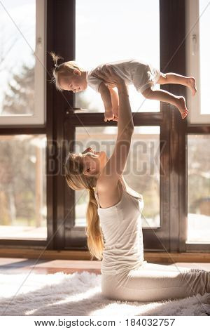 Young smiling attractive mother sitting near the floor window, holding baby daughter high, feeling alive, playing, working out, enjoying morning time together. Healthy lifestyle concept photo