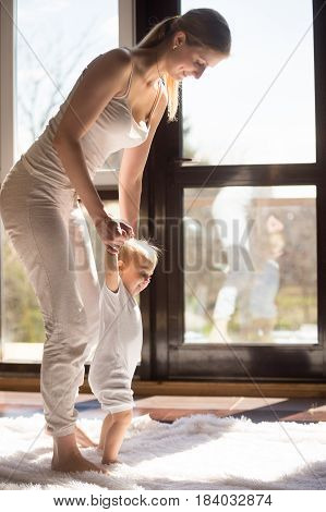 Baby girl making her first steps, learning to stand and walk through loving interaction and fun with mother at home, wearing white home wear, feeling happy and secure. Healthy lifestyle concept photo