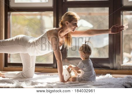 Young yogi smiling mother working out, doing Bird dog pose, wearing white sportswear, her baby daughter playing near her, yoga practice at home when having no time for gym. Healthy lifestyle concept