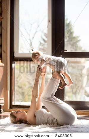 Young attractive sporty mother working out with her baby daughter, exercising at home wearing white sportswear, , leg lifting with baby,  postnatal exercise for abs. Healthy lifestyle concept photo