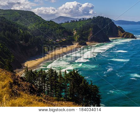 Oregon coast at Cape Meares with breaking waves and green hillsides