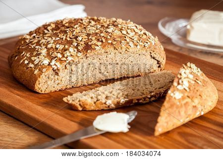 Healthy rye-wheat sourdough bread. Homemade whole grain fitness bread sprinkled with oat flakes closeup