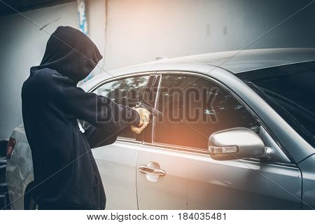A Robber Dressed In Black Pointing A Gun At A Driver In A Car. Car Thief Concept.