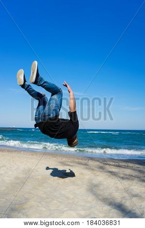 portrait of young parkour man doing flip or somersault on the beach. Freezed moment - finishing of flip