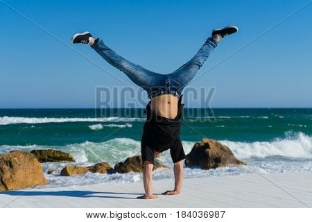 Young Athlete doing two hands handstand on the beach. Street workout. break dancer man on white wooden floor