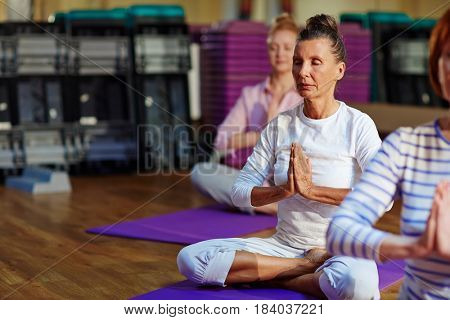 Cross-legged female keeping her palms together on chest during meditation