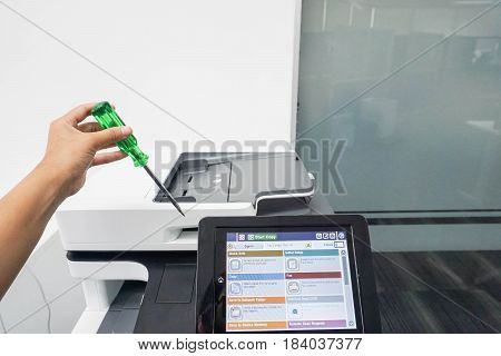 close up service engineer with screwdriver to repair and maintenance office printer
