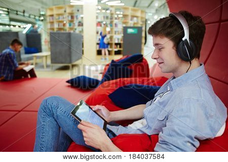 Modern student with headphones listening to music and reading e-book