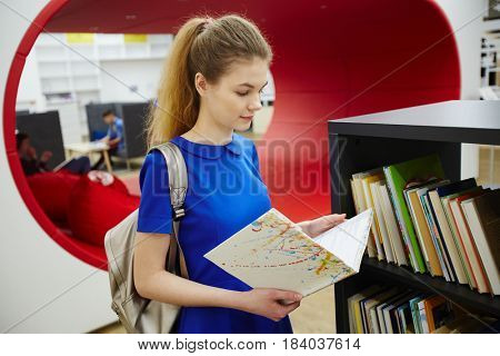 Clever girl with open book reading in library