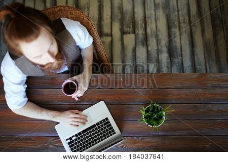 Modern designer with laptop sitting by table and working online