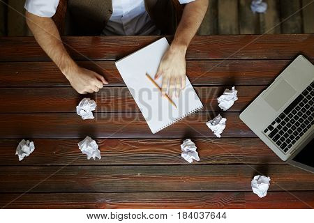 Wooden table with crumpled papers, laptop and notepad with pencil during work of creative designer