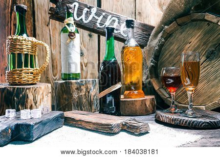 Wine bottles and wineglasses on raw wood bar counter or showcase. Natural stumps, burlap, oak barrel and rustic serving boards. Wooden signboard with text 'Wine'